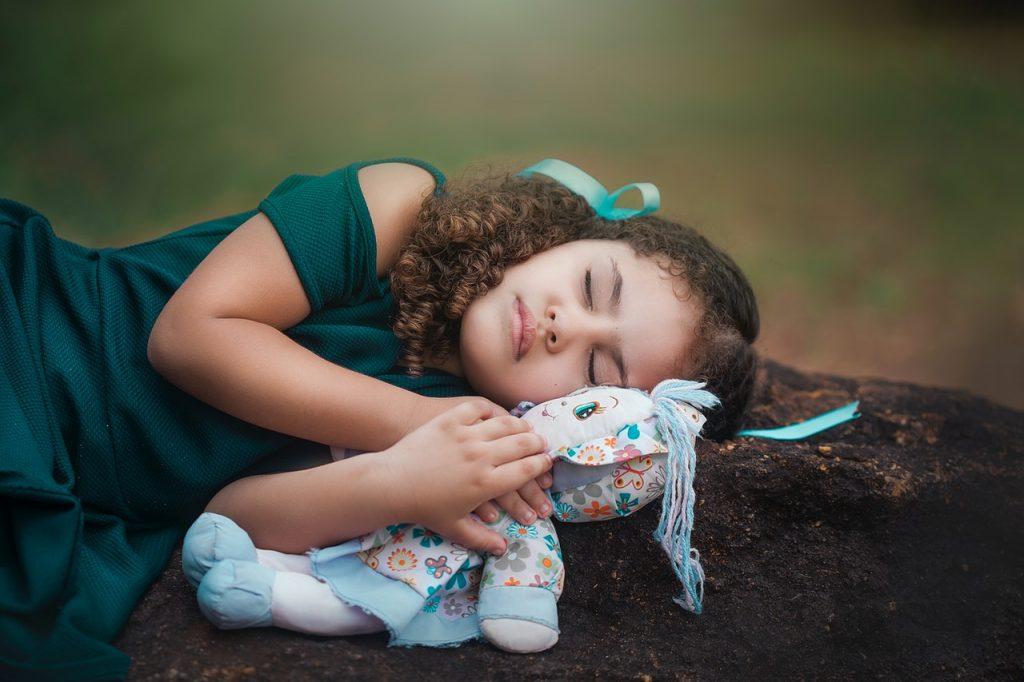 petite fille endormie avec sa poupée dans les bras