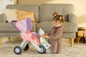 petite fille qui joue avec un poupon et une poussette